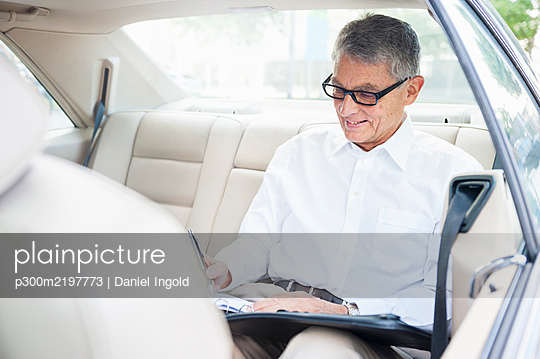 Smiling senior businessman working on back seat of car - p300m2197773 by Daniel Ingold