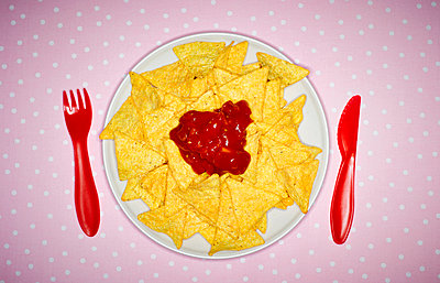 Plate of cheese nachos with salsa and red plastic cutlery on pink cloth - p300m1029025f by Kai Schwabe