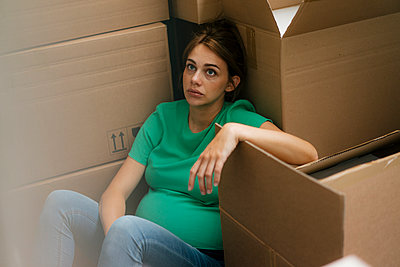 Exhausted pregnant woman sitting on floor surrounded by cardboard boxes  - p300m2228427 by Kniel Synnatzschke
