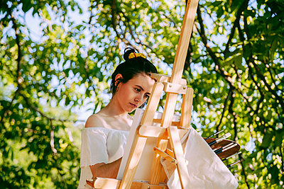 Madrid, SpainYoung woman artist painting a picture with her notebook and easel in the field - p300m2267814 von Manu Reyes