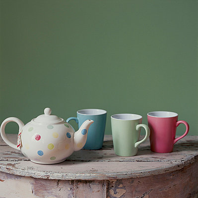 Teapot and mugs on a tabletop in pastel shades - p349m695232 by Emma Lee