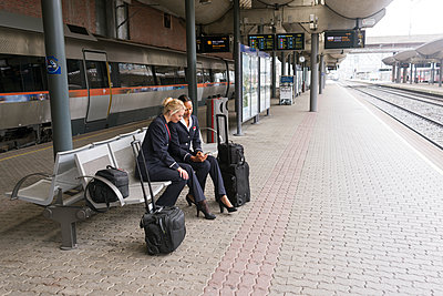 Norway, Oslo, Stewardesses sitting with suitcases - p352m1349862 by Viktor Holm