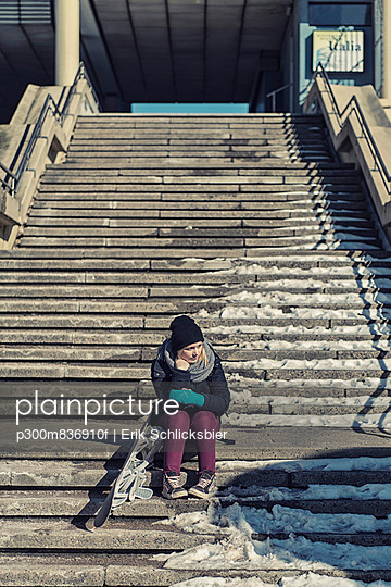Germany; Schleswig Holstein; Kiel; Young woman sitting on stairs besides snow board