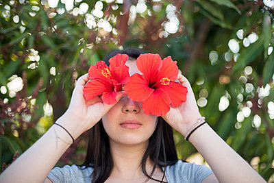 Girl with Hibiscus flowers in front of her eyes - p1580m2191502 by Andrea Christofi