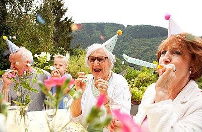Seniors celebrating birthday oarty in garden - p300m1205020 by Michelle Fraikin