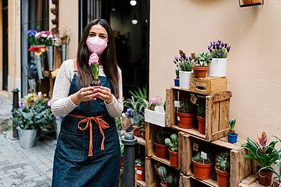 Valencia, Spain. Woman working in a florist's shop with a mask standing in the doorway of her shop. - p300m2274922 von Ezequiel Giménez