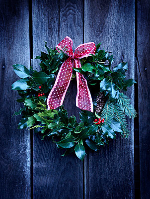 Wreath of holly with red bow on wooden door - p349m789864 by Brent Darby