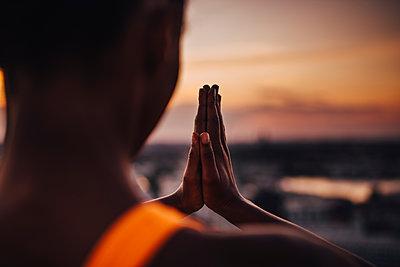 Female athlete practicing yoga during sunset - p426m2270537 by Maskot