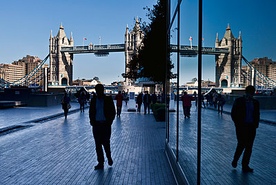 Pedestrians on a walkway with London's tower bridge in the background; London, England - p442m999143 by Doug McKinlay