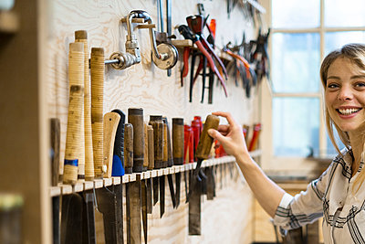 Woman holding hand tool in workshop - p623m2151667 by Frederic Cirou