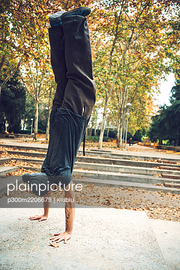 Young man doing handstand in public park during autumn season - p300m2206679 by klublu