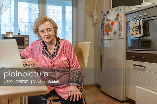 Senior woman sitting with laptop in kitchen at home - p300m2257371 by Vladimir Godnik