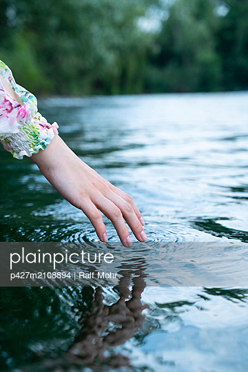 Woman touching the water - p427m2108894 by Ralf Mohr