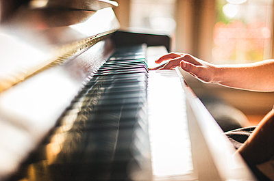 Cropped image of child's hand playing piano in a sunny room. - p1166m2153760 by Cavan Images
