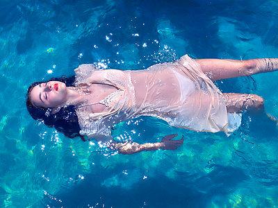 Frau mit Kleid im Pool - p1484m2289432 von Céline Nieszawer