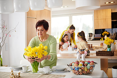 Senior woman arranging flowers on dining table with family in background - p300m1567641 by gpointstudio
