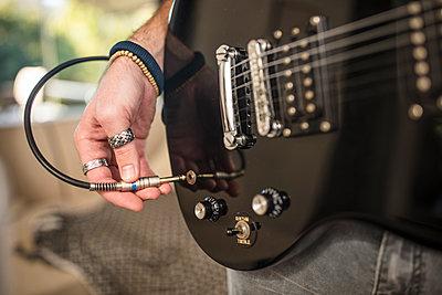 Close-up of man's hand plugging electric guitar - p300m2013298 von zerocreatives
