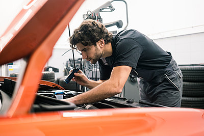 Car mechanic in a workshop working at car - p300m2166855 by Robijn Page