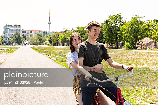 Young couple on a bike ride in a park - p294m2132925 by Paolo