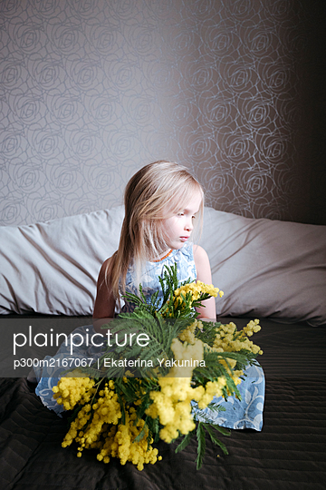 Portrait of blond little girl sitting on bed with bunch of mimosa - p300m2167067 von Ekaterina Yakunina