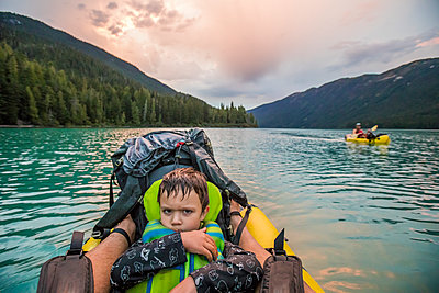 Young boy with grumpy face on a lake during paddling trip - p1166m2212557 by Cavan Images