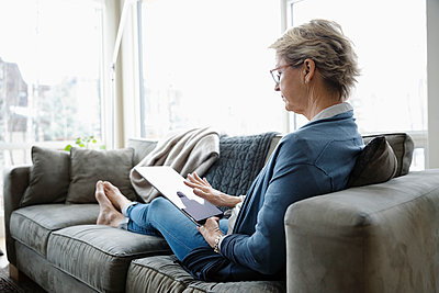 Mature woman using digital tablet on living room sofa - p1192m2088371 by Hero Images
