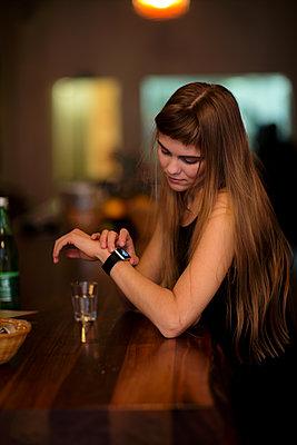 Junge Frau mit Smartwatch am Tresen - p1212m1084144 von harry + lidy