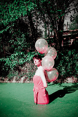 Woman in pink dress in a pond with balloons - p1521m2272079 by Charlotte Zobel
