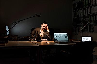 Businessman working in office at night - p300m1581120 von Uwe Umstätter