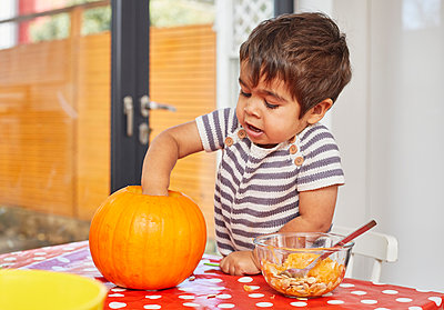 Boy gutting pumpkin in kitchen - p429m2091543 by Sverre Haugland