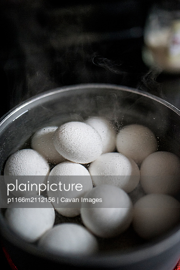 High angle view of eggs boiling in bowl at home during Easter - p1166m2112156 by Cavan Images