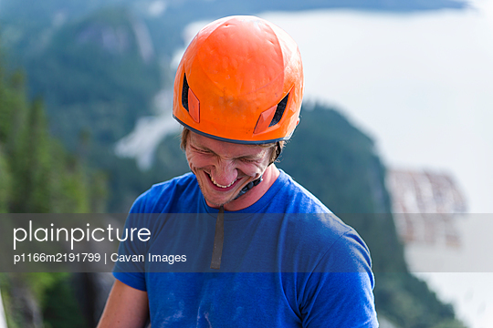 Climber with helmet smiling and laughing looking down above water - p1166m2191799 by Cavan Images