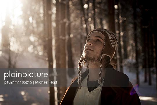 Junger Mann mit Wollmütze in einem Wald - p1324m1165215 von michaelhopf