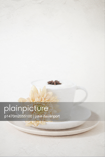 Chrysanthemum blossom beside cappuccino - p1470m2055100 by julie davenport