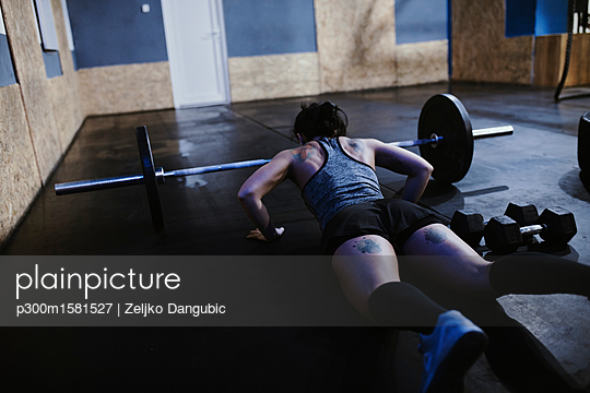 Woman doing push ups at barbell in gym - p300m1581527 von Zeljko Dangubic