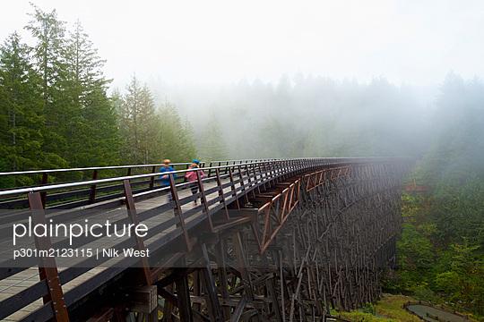 Kids running over railway trestle, British Columbia, Canada - p301m2123115 by Nik West
