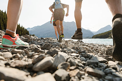 Friends running over rocks at sunny lakeside - p1192m2129226 by Hero Images