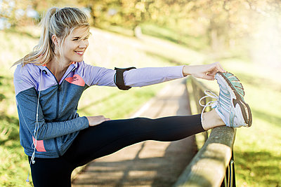 Female jogger stretching in park - p1520m2081896 by Michael Leckie