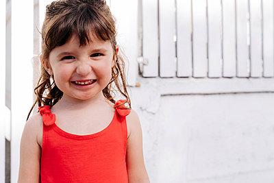 Portrait of little girl wearing red summer dress in front of white wall - p300m2202630 by Gemma Ferrando