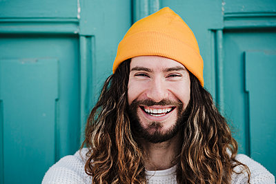 Cheerful male hipster wearing knit hat in front of door - p300m2274042 by Eva Blanco