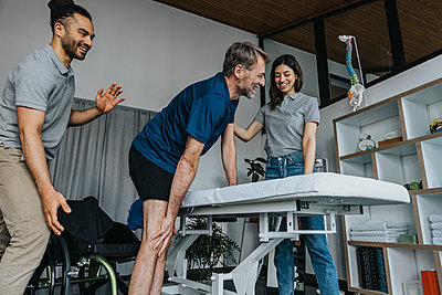 Smiling physiotherapists supporting male patient getting up from wheelchair in practice - p300m2276823 by Mareen Fischinger