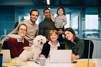 Portrait of smiling business team with kid and dog at creative office - p426m1588437 by Maskot