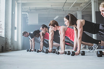 Athletes doing push-ups with dumbbells on floor - p555m1411970 by John Fedele
