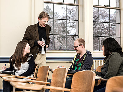 Teacher talking to students in classroom - p555m1479717 by Adam Crowley