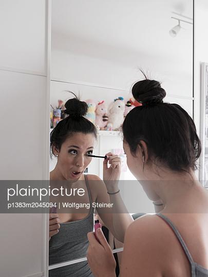 Junge Frau trägt Make-Up auf - p1383m2045094 von Wolfgang Steiner