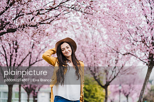 Smiling woman wearing sun hat while standing in front of trees during springtime - p300m2274807 by Eva Blanco