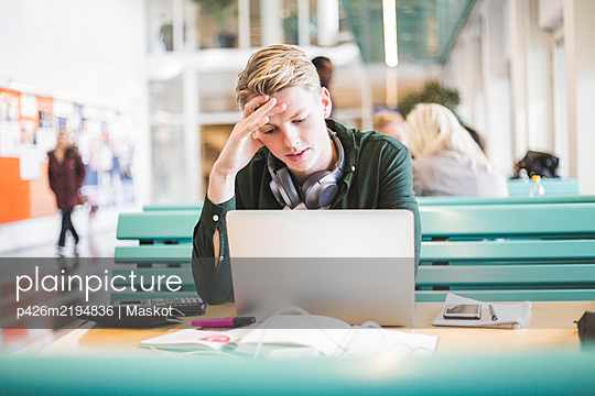 Young male student using laptop in cafeteria at university - p426m2194836 by Maskot