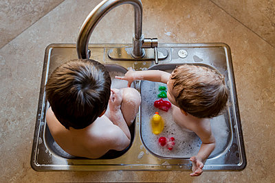 High angle view of brothers playing with water in sink - p1166m1210623 by Cavan Images