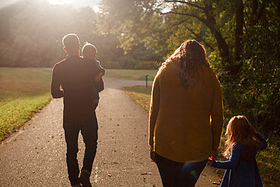 A family walks together holding hands in a park in the setting sun - p1166m2151928 by Cavan Images