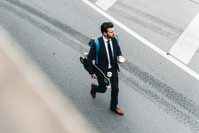 Businessman with takeaway coffee and skateboard walking on the street - p300m2004212 von Uwe Umstätter